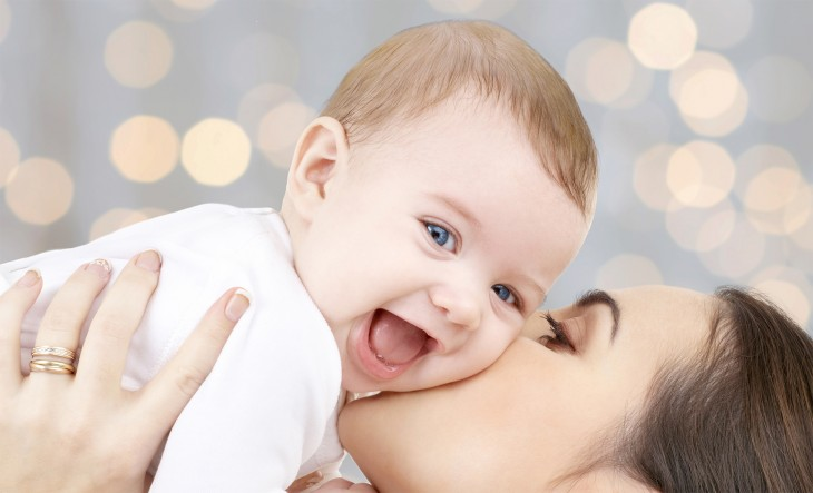 people, family, motherhood and children concept - happy mother hugging adorable baby over holidays lights background