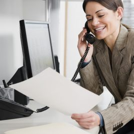 Businesswoman talking on phone while holding file